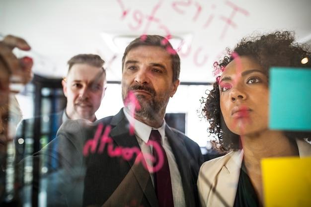 Wirtschaftler, die auf einer glaswand planen Kostenlose Fotos