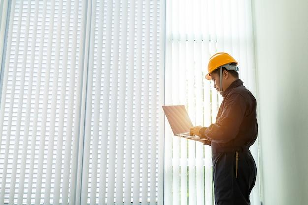 Wirtschaftsingenieur in der schutzhelm-tragenden sicherheitsjacke benutzt bildschirm- laptop. Premium Fotos