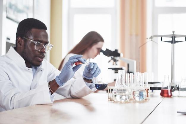 Wissenschaftler arbeiten im labor eng mit dem mikroskop zusammen, indem sie experimente und analysen durchführen. Kostenlose Fotos