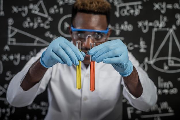 Wissenschaftler betrachten die orange und gelben chemikalien im glas im labor Kostenlose Fotos