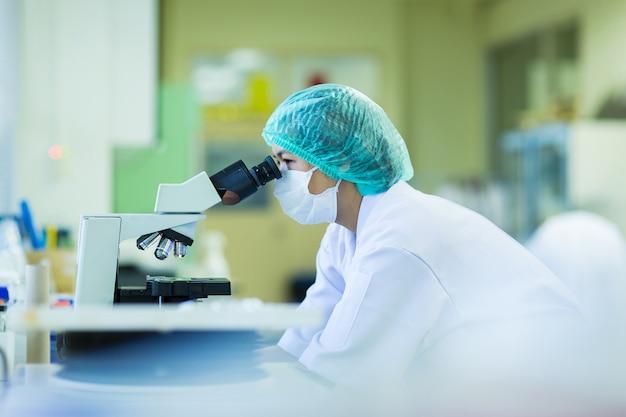 Wissenschaftler, der ein mikroskop in einem labor, in einer konzeptwissenschaft und in einer technologie verwendet Premium Fotos