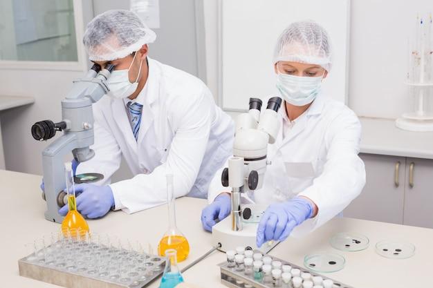 Wissenschaftler, die rohre mit mikroskop im labor überprüfen Premium Fotos