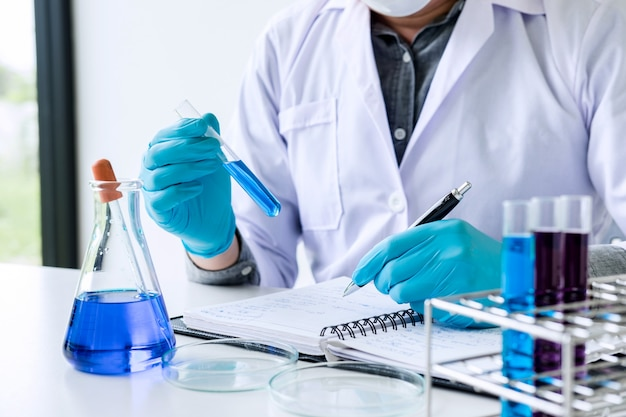 Wissenschaftler oder medizinisches im laborkittel, der reagenzglas mit reagens mit tropfen der farbflüssigkeit hält Premium Fotos