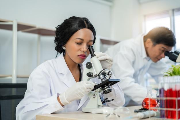 Wissenschaftler unter verwendung eines mikroskops im labor mit reagenzglashintergrund. medizinische gesundheitstechnologie und pharmazeutisches forschungs- und entwicklungskonzept Premium Fotos