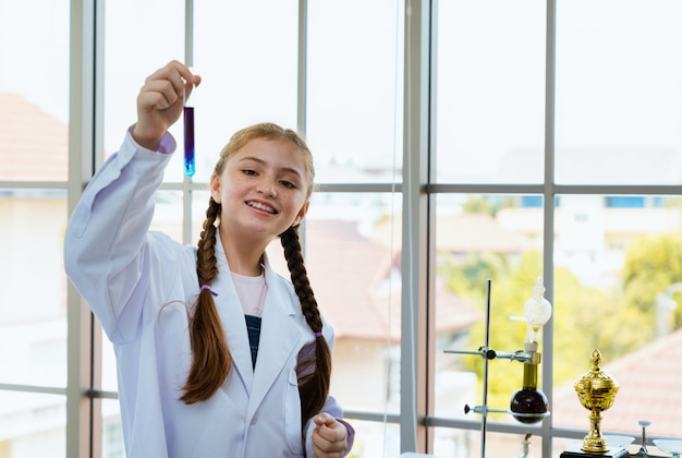 Wissenschaftlershowchemikalie des jungen mädchens mischte im glasgefäß im laborraum Premium Fotos