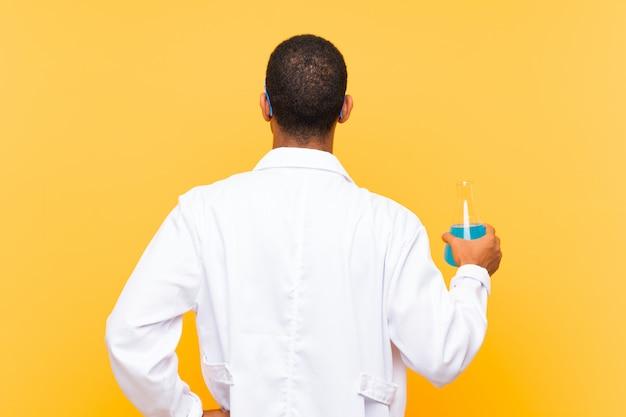 Wissenschaftlicher mann, der eine laborflasche in hinterer position hält Premium Fotos