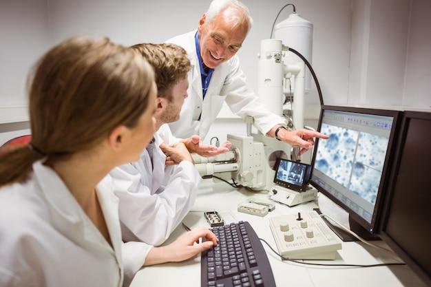 Wissenschaftsstudenten, die mikroskopisches bild auf computer mit lektor betrachten Premium Fotos