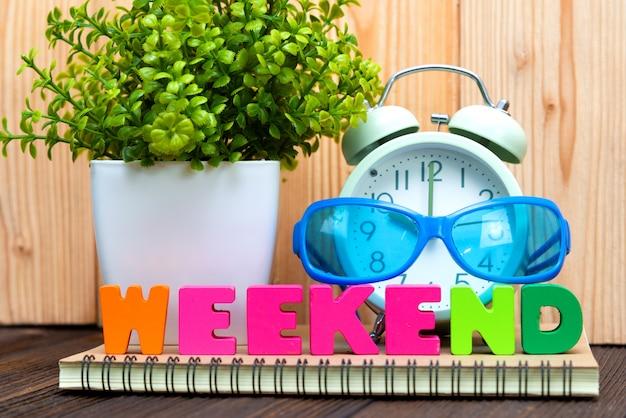 Wochenend-text und notizpapier, wecker und bäumchen Premium Fotos