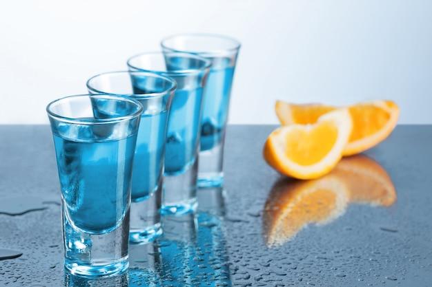 Wodka-glas mit eis auf blau Kostenlose Fotos