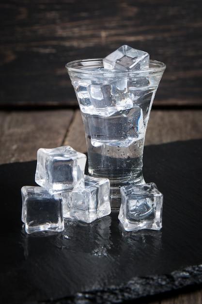 Wodka glas mit eis auf holztisch. Premium Fotos