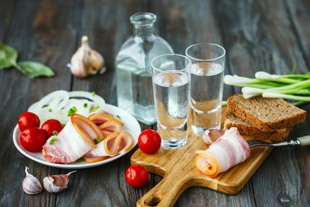 Wodka mit schmalz und frühlingszwiebeln auf holztisch Kostenlose Fotos