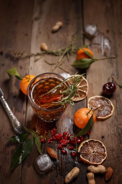 Wohlriechender fruchttee mit tangerinen, getrockneten zitronen und rosmarin auf einem holztisch. landhausstil. Premium Fotos