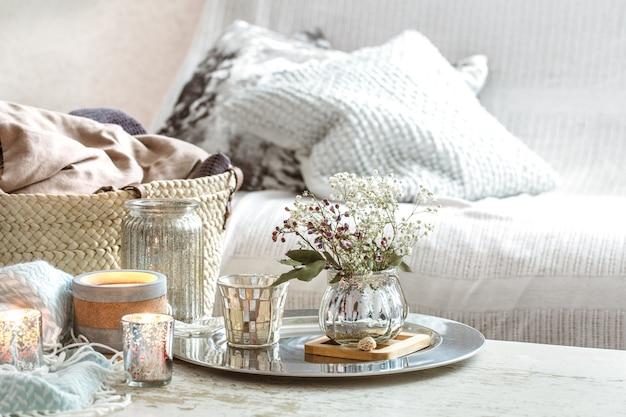 Wohnaccessoires im innenraum. eine türkisfarbene decke und ein weidenkorb mit einer vase mit blumen und kerzen Kostenlose Fotos