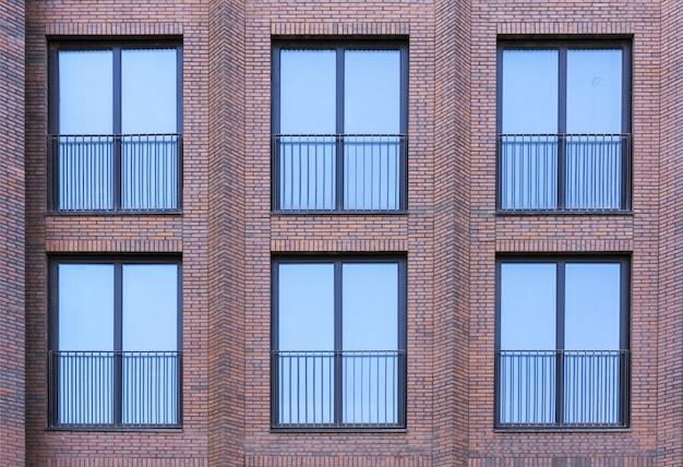 Wohngebäude im loft-stil. große fenster in einer roten backsteinmauer. Premium Fotos