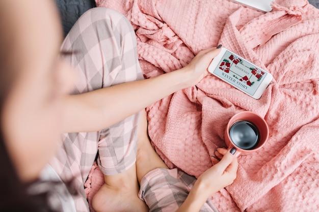 Wohnkomfort auf dem bett in der modernen wohnung der hübschen frau, die film am telefon sieht. blick von oben frau mit tasse kaffee genießen häusliche harmonie, wochenenden, guten morgen auf rosa decke Kostenlose Fotos