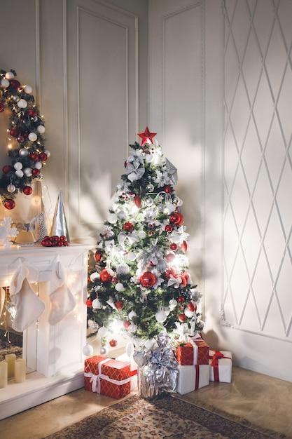 Wohnzimmer mit weihnachtsbaum mit spielzeug und girlanden verziert Premium Fotos