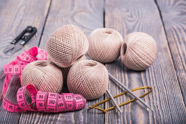 Wollknäuel, stricknadeln und maßband auf einer holzoberfläche. Premium Fotos