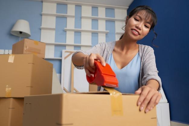 Woman sealing umzugskarton Kostenlose Fotos