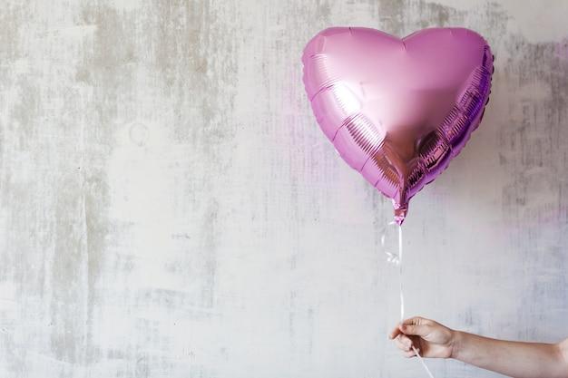 Wonans hand hält einen rosa herzballon auf grauem betonhintergrundkopierraum Premium Fotos