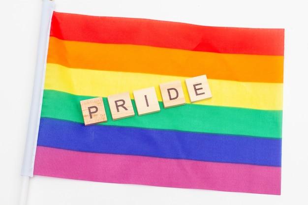 Word pride aus holzwürfeln auf einer lgbt-stolzfahne. Premium Fotos