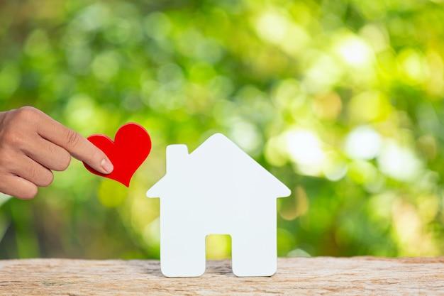 World habitat day, nahaufnahmebild eines modellhauses und hand, die papierherz hält Kostenlose Fotos