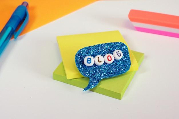 Wort des blogs aus kunststoffperlen in einem strahlend blauen sprechblasen-schreibwarenzubehör Premium Fotos