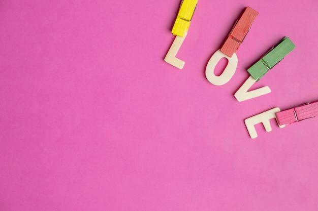 Wort liebe in den roten herzen auf rosa hintergrund, liebesikone, valentinstag, beziehungskonzept Premium Fotos