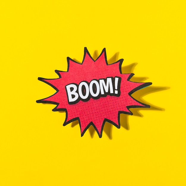 Wortboom! in retro comic-sprechblase auf gelbem hintergrund Kostenlose Fotos