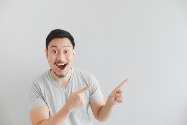 Wow und überraschtes gesicht des mannes im grauen t-shirt mit handpunkt auf leerem raum. Premium Fotos