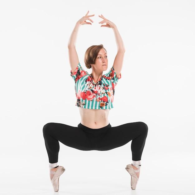 Würdevolle ballerina, die gegen weißen hintergrund aufwirft Kostenlose Fotos