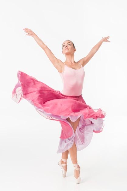 Würdevolle ballerina im rosa ballettröckchen, das gegen weißen hintergrund aufwirft Kostenlose Fotos