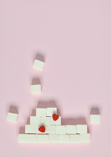 Würfel des raffinierten zuckers auf einem rosa hintergrund. was sind die konzepte von diabetes und kalorienzufuhr Premium Fotos
