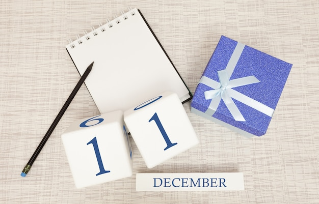 Würfelkalender für den 11. dezember und geschenkbox, in der nähe eines notizbuches mit bleistift Premium Fotos