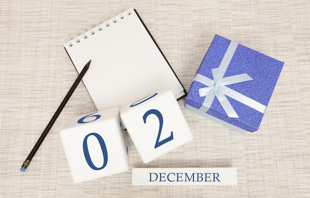 Würfelkalender für den 2. dezember und geschenkbox, in der nähe eines notizbuchs mit einem bleistift Premium Fotos