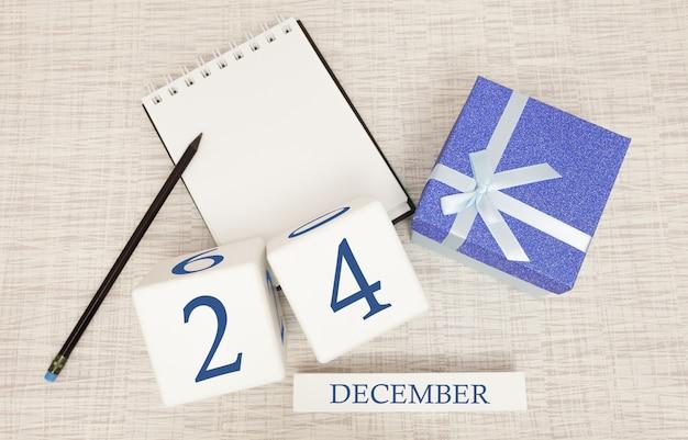 Würfelkalender für den 24. dezember und geschenkbox, in der nähe eines notizbuchs mit einem bleistift Premium Fotos