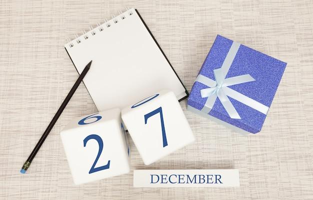 Würfelkalender für den 27. dezember und geschenkbox, in der nähe eines notizbuches mit bleistift Premium Fotos