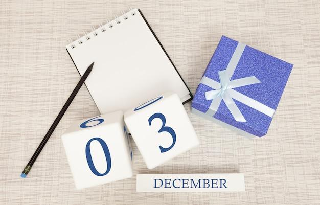 Würfelkalender für den 3. dezember und geschenkbox, in der nähe eines notizbuchs mit einem bleistift Premium Fotos