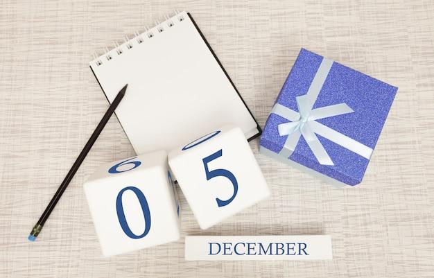 Würfelkalender für den 5. dezember und geschenkbox, in der nähe eines notizbuchs mit einem bleistift Premium Fotos