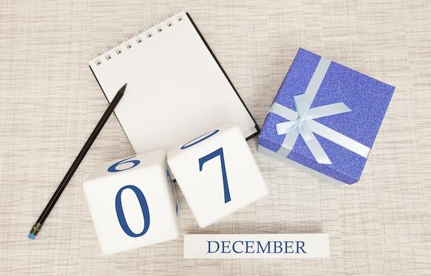 Würfelkalender für den 7. dezember und geschenkbox, in der nähe eines notizbuchs mit einem bleistift Premium Fotos