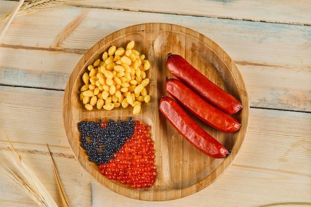Würstchen, gekochte maissamen und kaviar auf einem holzteller. Kostenlose Fotos