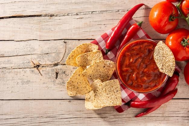 Würzige chilisauce in der schüssel mit nacho-chips auf holztisch Premium Fotos