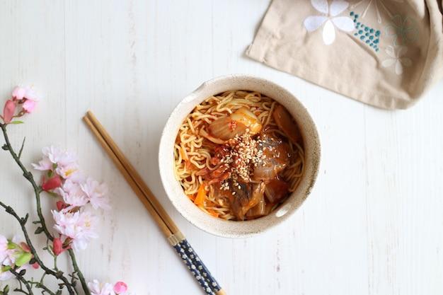 Würzige ramen-nudeln mit pilz und kimchi auf der schüssel mit stäbchen Premium Fotos