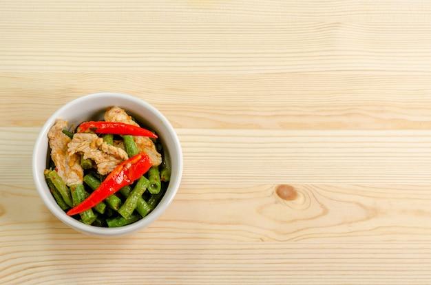 Würziger aufruhr gebratenes schweinefleisch mit roter currypaste und langer bohne yard, thailändisches lebensmittelmenü Premium Fotos