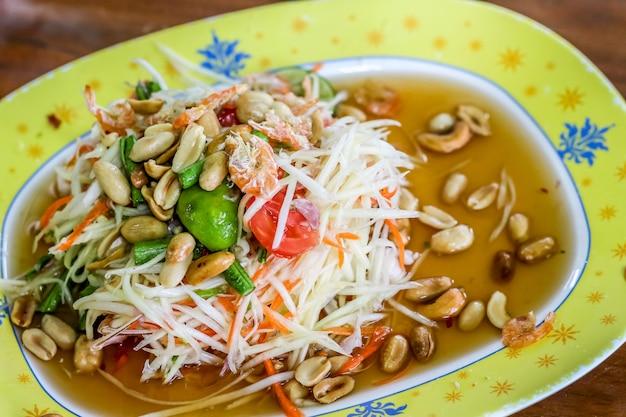 Würziger grüner papayasalat der thailändischen art (som tum thailändisch) in der gelben platte Premium Fotos