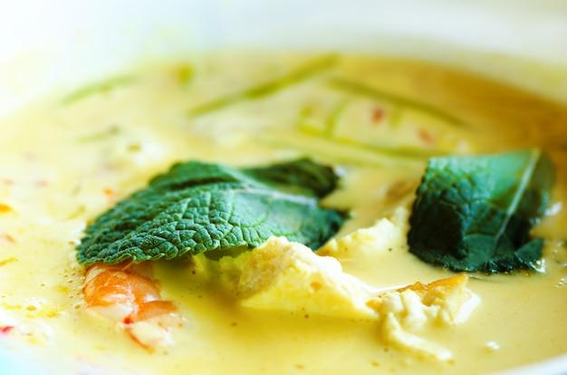 Würziger kokosmilchcremesuppe-curry mit hühnerfleisch, tigergarnelen, langen sojanudeln, sojasprossen, limette Premium Fotos