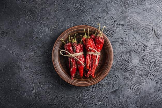 Würziger paprika auf einem dunklen hintergrund in den keramischen platten Premium Fotos