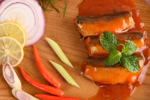 Würziger salat der sardine in der tomatensauce auf hölzernem behälter Kostenlose Fotos