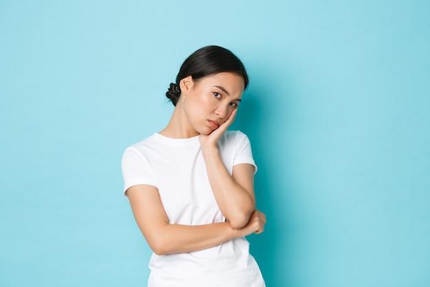 Wütend und gelangweilt schmollendes süßes asiatisches mädchen, das sich auf die handfläche stützte und gleichgültig aussah, sich nicht besorgt verhielt, sondern wütend oder beleidigt die stirn runzelte und den blauen hintergrund missfiel. Premium Fotos