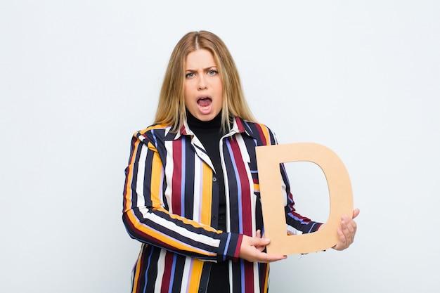 Wütend, wütend, nicht einverstanden, den buchstaben d des alphabets haltend, um ein wort oder einen satz zu bilden. Premium Fotos