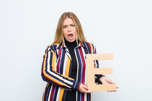 Wütend, wütend, nicht einverstanden, den buchstaben e des alphabets haltend, um ein wort oder einen satz zu bilden. Premium Fotos